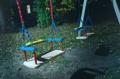 在街道在晚上,童年的结尾,寂寞的悲伤的概念的空的儿童` s摇摆 库存图片
