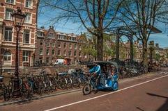 在街道在运河旁边和老大厦上的人力车骑马在晴天在阿姆斯特丹 免版税库存照片