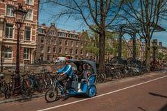 在街道在运河旁边和老大厦上的人力车骑马在晴天在阿姆斯特丹 免版税库存图片