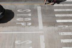 在街道小心黑色汽车司机的白色交通停车牌停止在横穿线,两个人横渡的行人穿越道 图库摄影