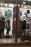 在街道服装店的季节性销售开放在游人的晚上 免版税库存图片