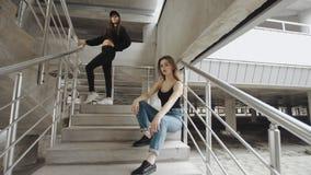 在街道样式衣物photoshoot的女性模型在具体台阶,摆在nto照相机的女孩 股票视频