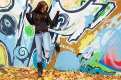 在街道画墙壁附近的女孩 免版税库存照片