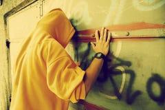 在街道画grunge墙壁上的年轻人 免版税库存图片