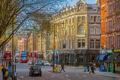 在街道的一个交叉点的伦敦交通在早晨lig的 免版税库存图片