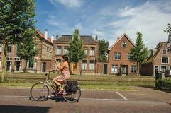 在街道的妇女踩的踏板的自行车在渠道边缘在晴天在韦斯普 免版税库存照片