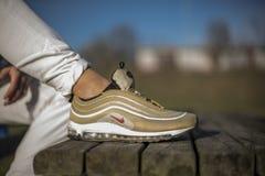 在街道的耐克空气最大97双金鞋子 免版税库存图片