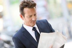 在街道的英俊的商人读书报纸 库存图片