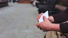 在街道的调动贿款 一个人与金钱的一个信封为贿赂做准备,等待紧张坐a 股票录像