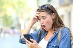 在街道的震惊青少年的检查的电话内容 免版税图库摄影