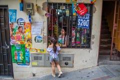 在街道边商店的小女孩买的糖果 免版税库存照片