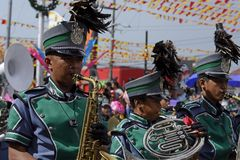 在街道陈列的男性乐队成员戏剧萨克斯管在每年军乐队陈列时 免版税库存照片