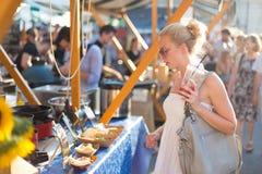 在街道食物节日的妇女买的膳食 免版税图库摄影