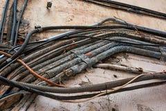 在街道,恶劣的接线的危险上的老缆绳 免版税库存图片
