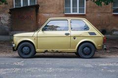 在街道,金子颜色的减速火箭的菲亚特126 免版税库存照片