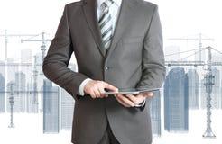 在衣服举行片剂个人计算机的商人 免版税库存图片