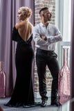 在衣服和晚礼服的年轻美好的夫妇 免版税库存图片