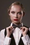 在衣服和蝶形领结打扮的妇女 免版税库存照片