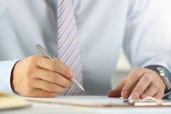 在衣服和领带举行银的男性胳膊 免版税库存照片