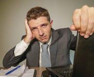 在衣服和领带工作的年轻沮丧和被注重的商人被淹没在办公室手提电脑书桌遭受的头疼 免版税图库摄影