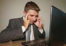 在衣服和领带工作的年轻沮丧和被注重的商人被淹没在办公室手提电脑书桌遭受的头疼 图库摄影
