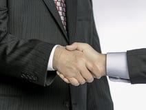 在衣服和领带的一对一握手;商人接近的观点  免版税库存照片