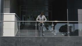 在衣服和领带的商人对商业中心调整他的站立在入口的衣裳 影视素材