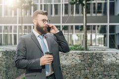 在衣服和领带的年轻商人在他的手机站立室外,饮用的咖啡并且谈话 人工作 免版税库存图片