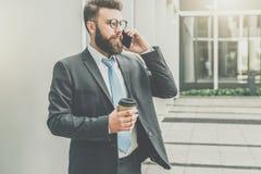 在衣服和领带的年轻商人在他的手机站立室外,饮用的咖啡并且谈话 图库摄影