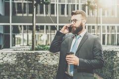 在衣服和领带的年轻商人在他的手机站立室外,饮用的咖啡并且谈话 免版税库存照片