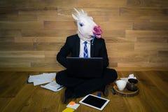 在衣服和领带的独角兽在家热心地运作有一支铅笔的办公室在牙 免版税库存图片