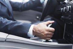 在衣服改变的齿轮的商人在汽车 免版税库存图片