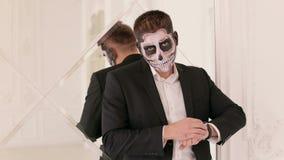 在衣服有头骨构成的打扮的一个人的画象,对镜子墙壁 影视素材
