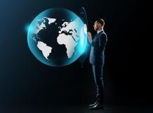 在衣服的商人与真正地球投射 免版税库存图片