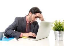 在衣服的商人和领带在运转的办公桌坐计算机 免版税库存照片