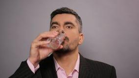 在衣服的商人喝矿泉水的在合作会议,干渴上 影视素材