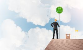 在衣服的商人在与生态概念牌的房子上面 混合画法 库存照片