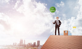 在衣服的商人在与生态概念牌的房子上面 混合画法 免版税库存图片