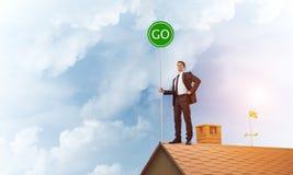 在衣服的商人在与生态概念牌的房子上面 混合画法 库存图片