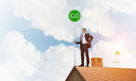 在衣服的商人在与生态概念牌的房子上面 混合画法 图库摄影