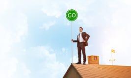 在衣服的商人在与生态概念牌的房子上面 混合画法 免版税库存照片