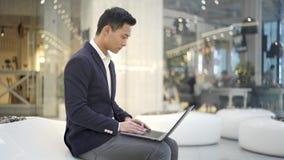 在衣服的年轻亚洲男性商人与在他的膝盖的膝上型计算机一起使用