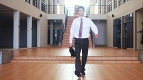 在衣服的年轻英俊的商人在商业中心走与一个公文包 通信,联络,新政 库存照片