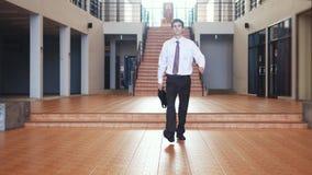 在衣服的年轻英俊的商人走与在businesscentre的一个公文包 通信,联络,新政 免版税库存照片