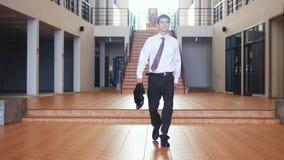 在衣服的年轻英俊的商人走与在businesscentre的一个公文包 通信,联络,新政 库存图片