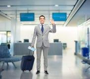 在衣服的愉快的商人与旅行袋子 免版税库存图片