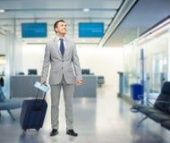 在衣服的愉快的商人与旅行袋子 免版税图库摄影