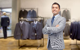 在衣服的愉快的商人在服装店 免版税库存图片