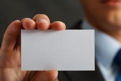 在衣服的拿着空白的名片的商人和手 库存照片
