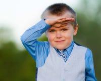 在衣服的男孩smilng 免版税图库摄影
